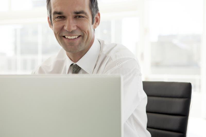 Glimlachende zakenman die aan laptop in bureau werken - portret royalty-vrije stock fotografie