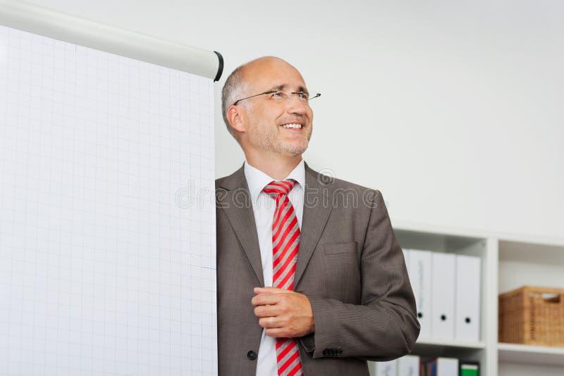Glimlachende zakenman die bij flipchart voorstellen stock afbeelding