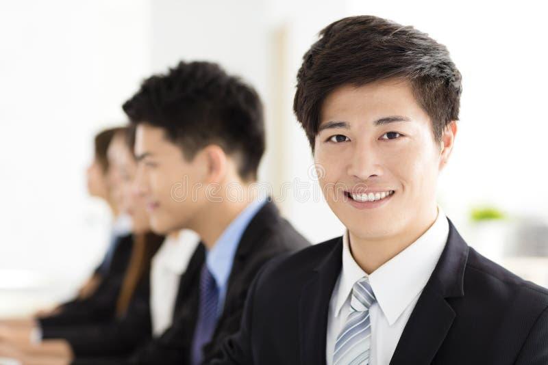 Glimlachende zakenman die camera met zijn collega bekijken royalty-vrije stock foto