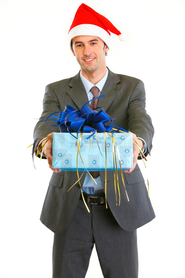 Glimlachende zakenman die in de Hoed van de Kerstman gift voorstelt stock foto