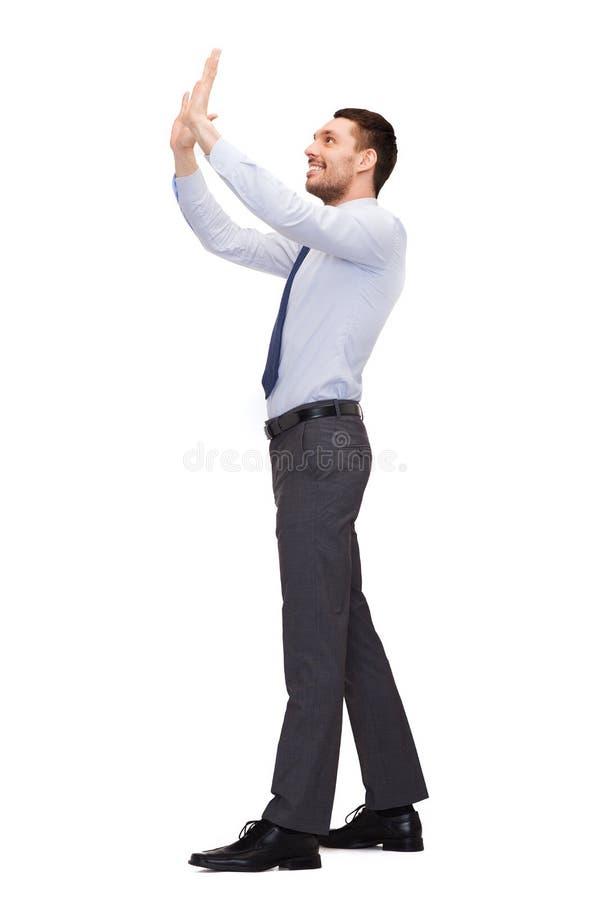 Glimlachende zakenman die denkbeeldig iets verhogen stock fotografie