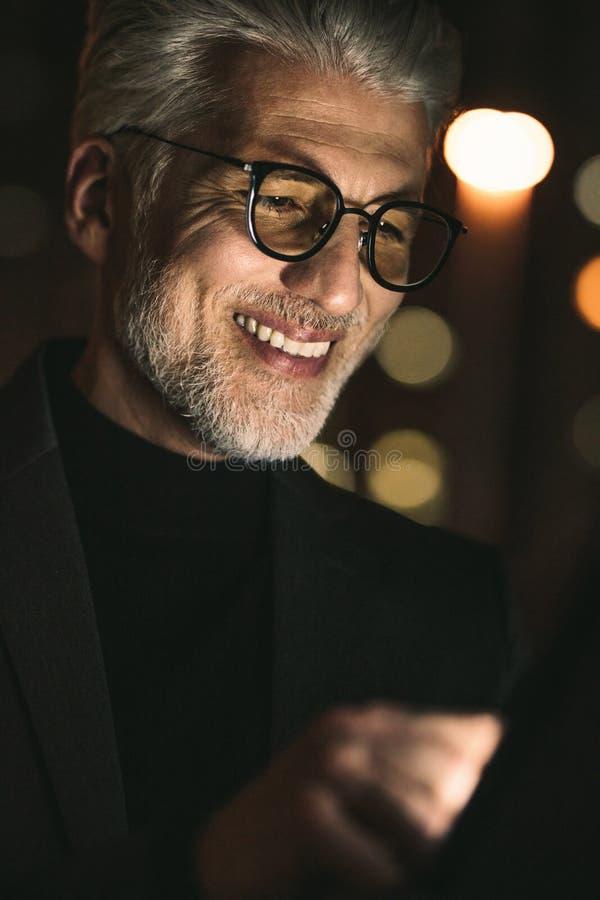 Glimlachende zakenman die digitale tablet in bureau gebruiken stock foto