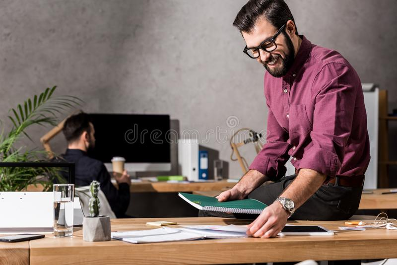 glimlachende zakenman die documenten nemen van stock foto's