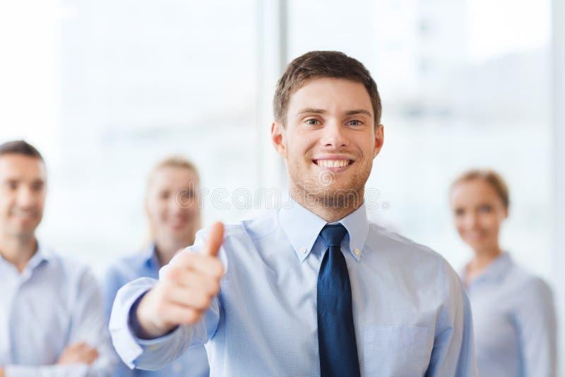 Glimlachende zakenman die duimen in bureau tonen royalty-vrije stock foto's