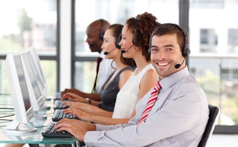 Glimlachende zakenman die in een call centre werkt stock afbeelding