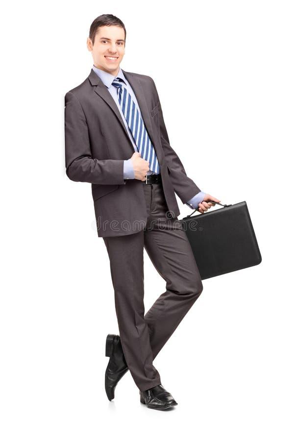 Glimlachende zakenman die een leeraktentas houden en agai leunen royalty-vrije stock foto's