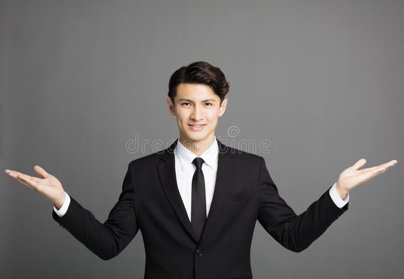 Glimlachende zakenman die iets introduceren stock foto's