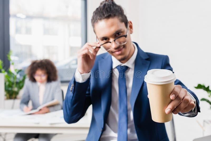 Glimlachende zakenman die koffie aanbieden stock afbeelding