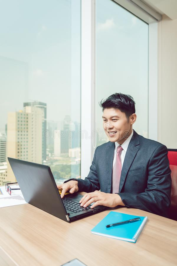 Glimlachende zakenman die laptop met behulp van royalty-vrije stock fotografie
