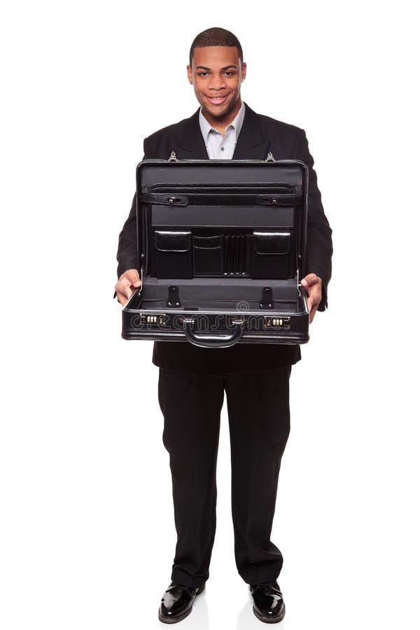 Glimlachende zakenman die lege open aktentas houdt stock foto's