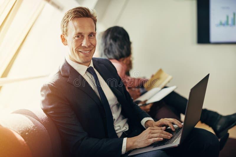 Glimlachende zakenman die met laptop tijdens een prese bureau werken stock afbeeldingen