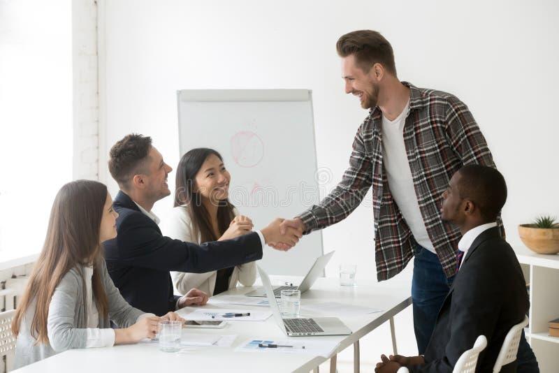 Glimlachende zakenman die nieuwe partner welkom heten op groepsvergadering met stock afbeelding