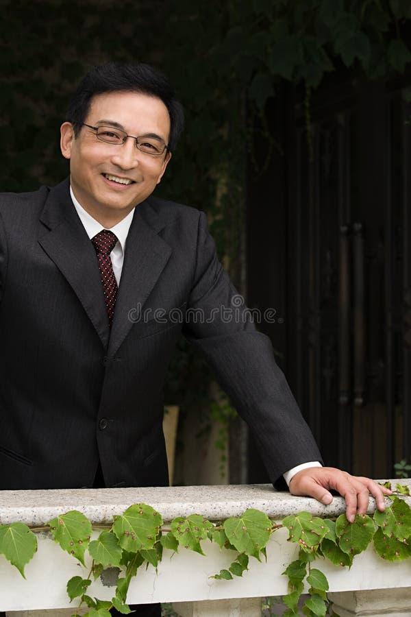 Glimlachende zakenman die op een richel leunt stock foto