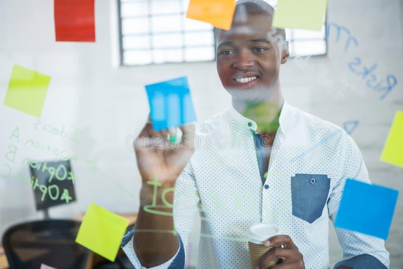 Glimlachende zakenman die op kleverige nota's schrijven royalty-vrije stock afbeelding