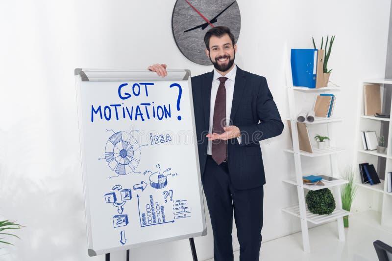glimlachende zakenman die op whiteboard met de gekregen bedrijfsgrafieken van de motivatieinschrijving richten en royalty-vrije stock foto