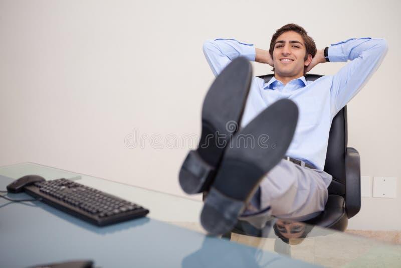 Glimlachende zakenman die terug als zijn voorzitter leunt royalty-vrije stock fotografie