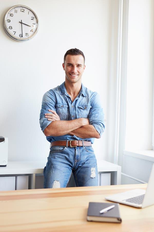 Glimlachende zakenman die zich in bureau met gekruiste wapens bevinden stock fotografie