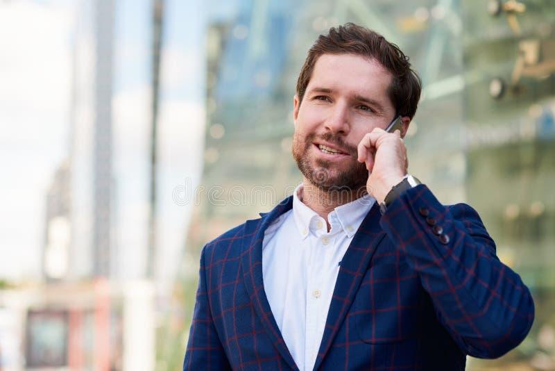 Glimlachende zakenman die zich in de stad bevinden die op een cellphone spreken stock afbeeldingen