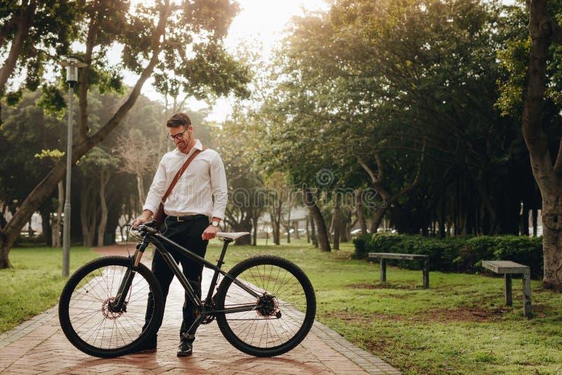 Glimlachende zakenman die zich in park met zijn fiets bevinden stock afbeelding