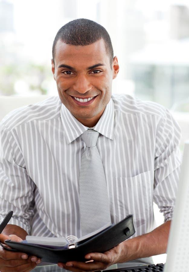 Glimlachende zakenman die zijn agenda raadpleegt stock foto's