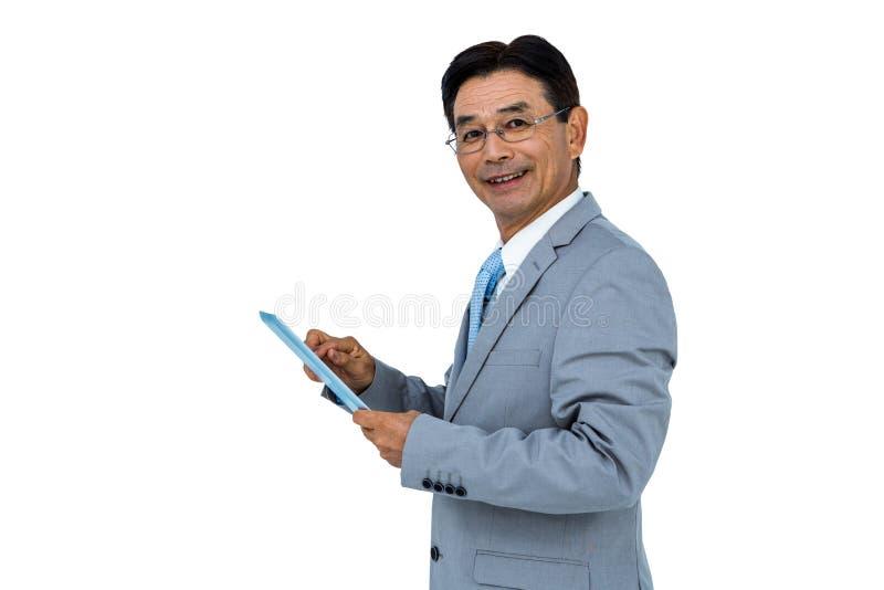 Glimlachende zakenman die zijn tablet gebruiken royalty-vrije stock foto