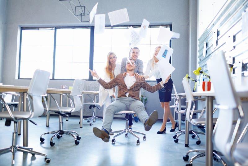 Glimlachende zakenman en arbeiders die weg documenten op de bureauachtergrond werpen Samenwerkingsconcept royalty-vrije stock foto's