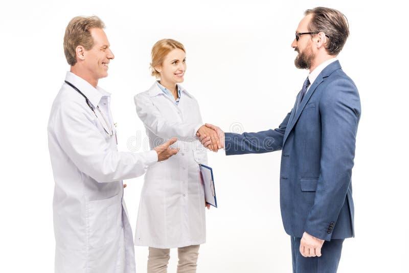 glimlachende zakenman en artsen die elkaar begroeten stock foto's