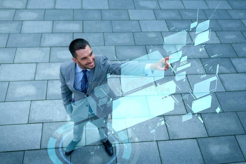 Glimlachende zakenman met de virtuele schermen in openlucht stock afbeeldingen