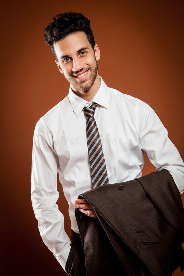 Glimlachende zakenman met jackt in zijn handen stock fotografie
