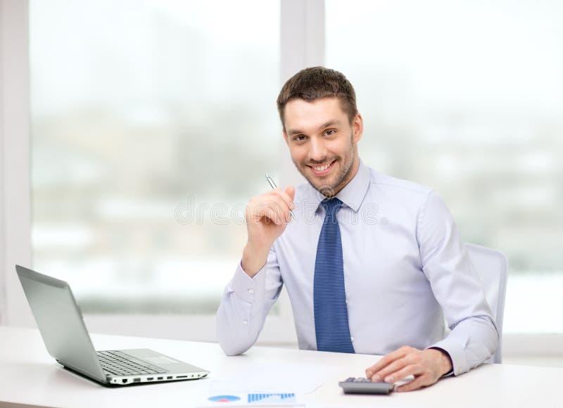 Glimlachende zakenman met laptop en documenten stock afbeelding