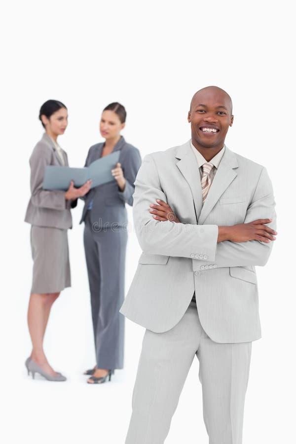 Glimlachende zakenman met medewerkers achter hem royalty-vrije stock afbeeldingen