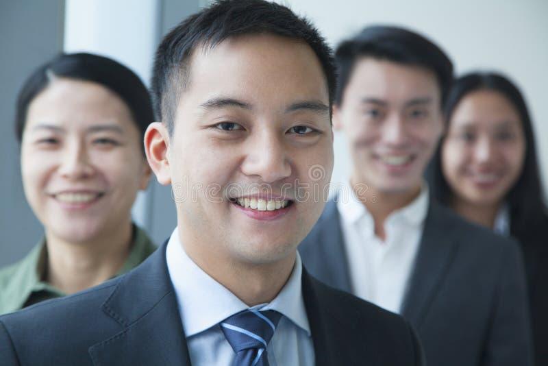 Glimlachende Zakenman met medewerkers in bureauportret stock afbeelding