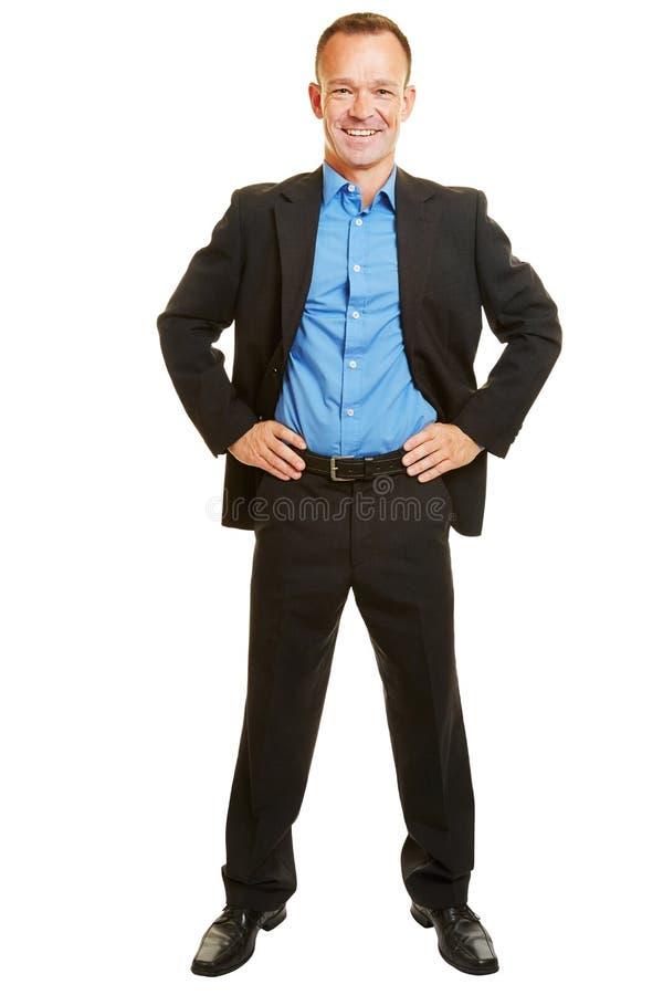 Glimlachende zakenman met zijn met de handen in de zij wapens royalty-vrije stock afbeelding