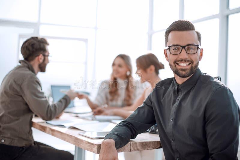 Glimlachende zakenman op de achtergrond van het bureau royalty-vrije stock afbeelding