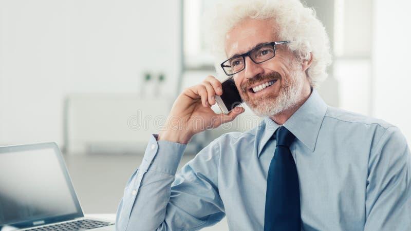 Glimlachende zakenman op de telefoon royalty-vrije stock afbeelding