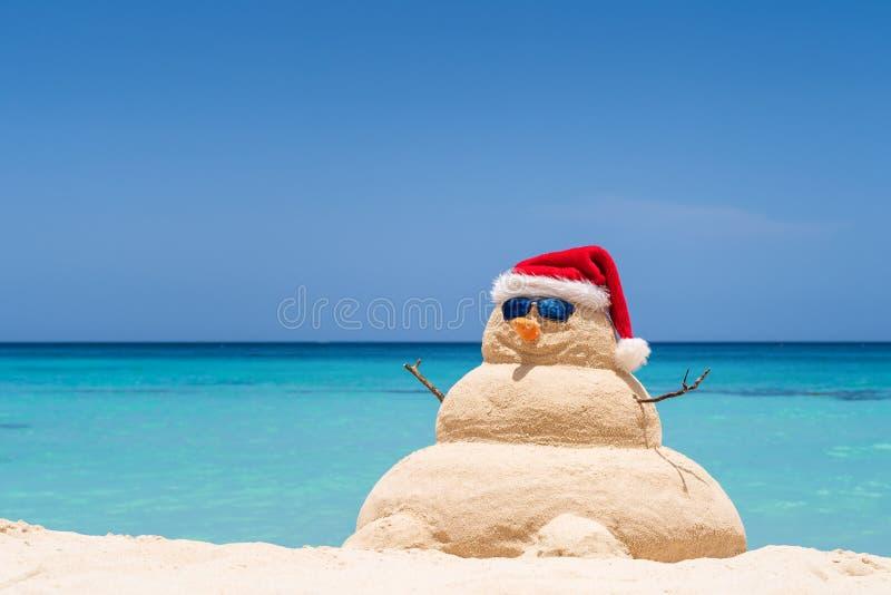 Glimlachende zandige sneeuwman met rode santahoed op het Caraïbische strand Vakantieconcept voor Nieuwjaar en Kerstkaarten stock afbeelding