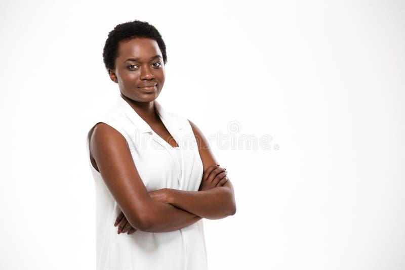 Glimlachende zekere Afrikaanse Amerikaanse jonge vrouw die zich met gekruiste wapens bevinden stock foto