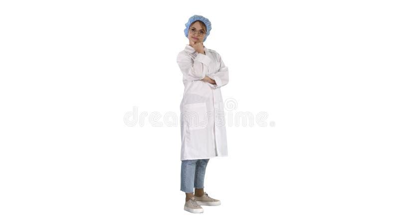 Glimlachende zekere jonge vrouw arts die zich met die wapens bevinden over op witte achtergrond worden gekruist stock foto's