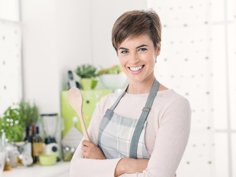 Glimlachende zekere jonge vrouw met schort het stellen in de keuken royalty-vrije stock afbeelding