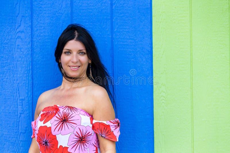 Glimlachende zekere jonge vrouw tegen blauw hout stock afbeeldingen