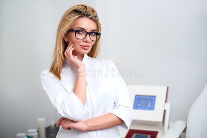 Glimlachende zekere vrouwelijke schoonheidsspecialist arts in laboratoriumlaag die in haar bureau met medische hardware en geduld stock afbeeldingen