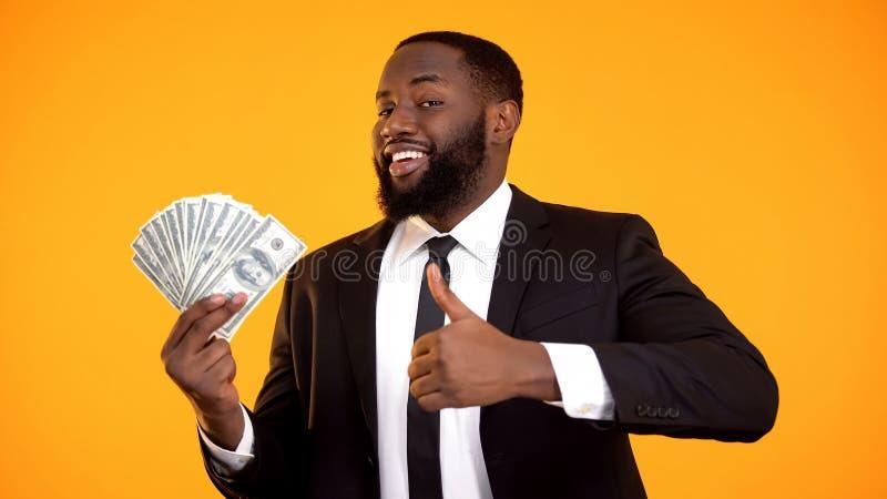 Glimlachende zekere zwarte zakenman die dollarrekeningen en duim-omhooggaand gebaar tonen stock fotografie