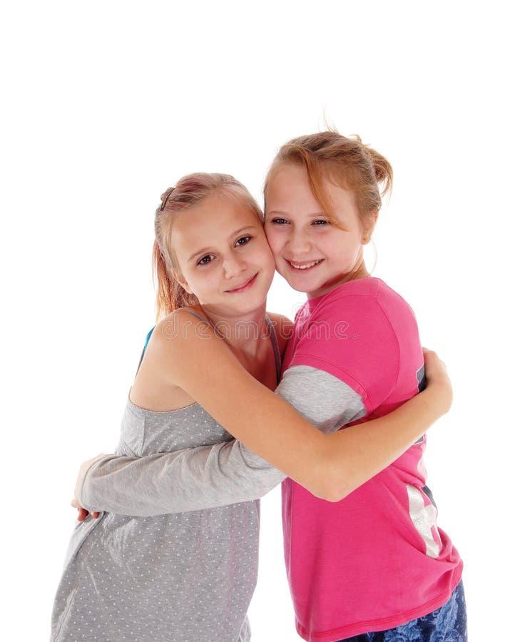 Glimlachende zusters die elkaar koesteren royalty-vrije stock afbeelding