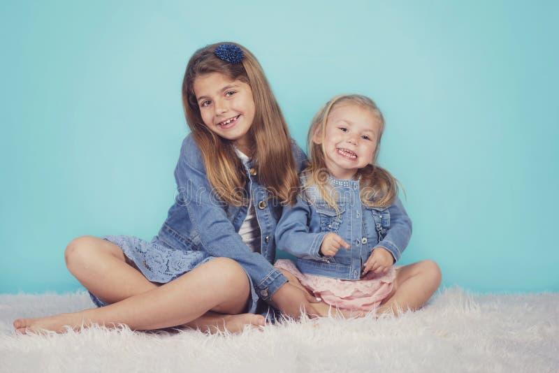 Glimlachende zusters die op de vloer zitten royalty-vrije stock afbeeldingen