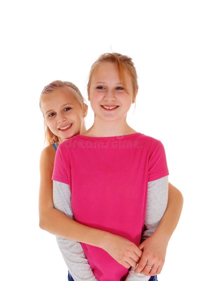 Glimlachende zusters die zich achter elkaar bevinden royalty-vrije stock afbeeldingen