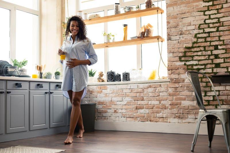 Glimlachende zwangere vrouw die in haar keuken lopen stock foto's
