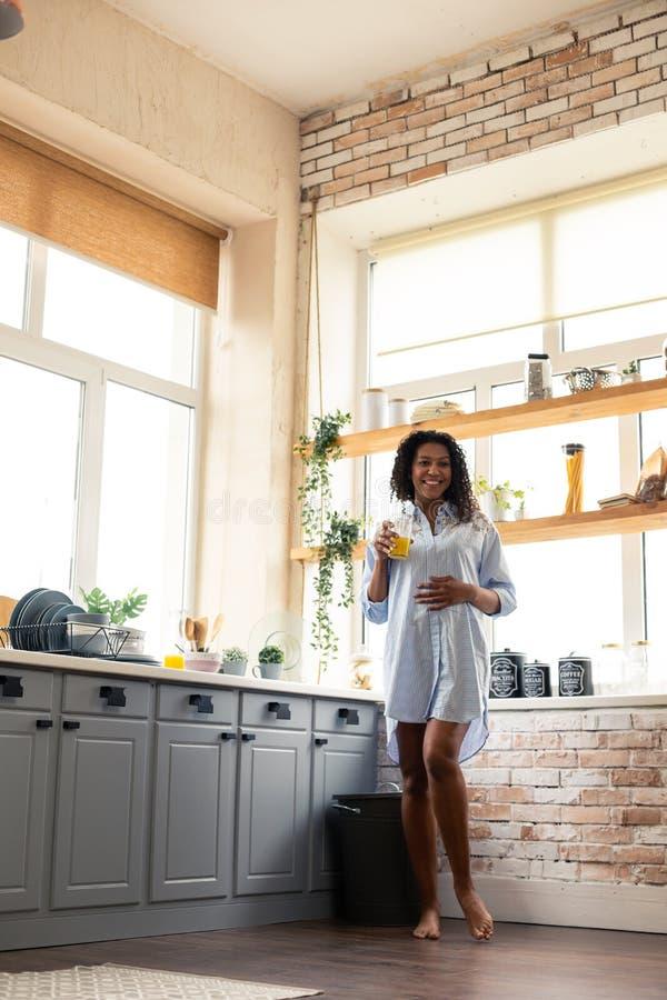 Glimlachende zwangere vrouw wat betreft haar buik in de keuken royalty-vrije stock foto's