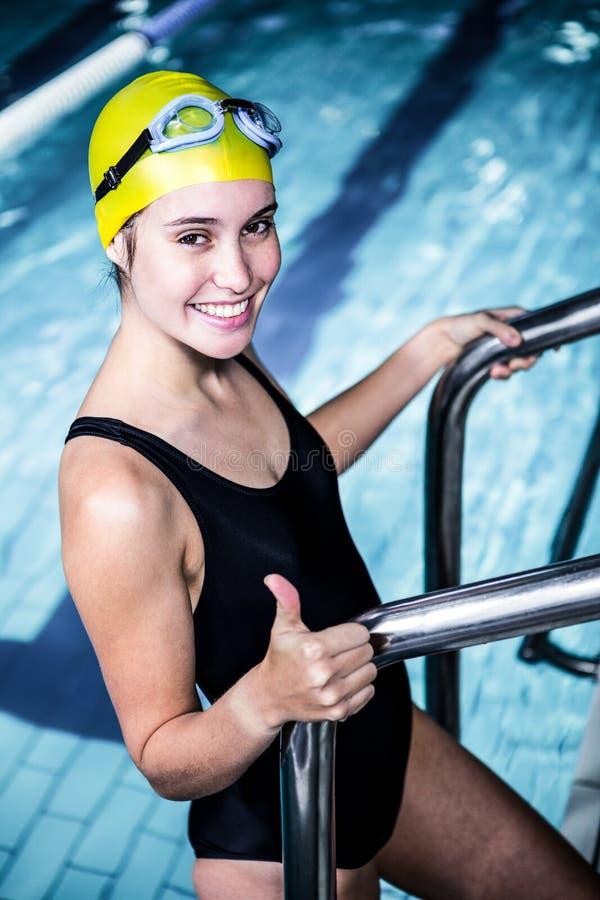 Glimlachende zwemmersvrouw die van het zwembad weggaan stock afbeelding