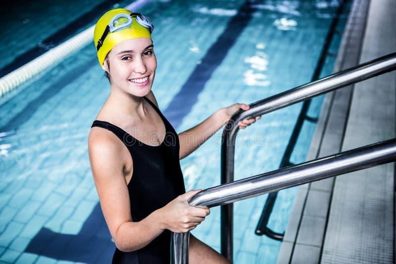 Glimlachende zwemmersvrouw die van het zwembad weggaan royalty-vrije stock afbeeldingen