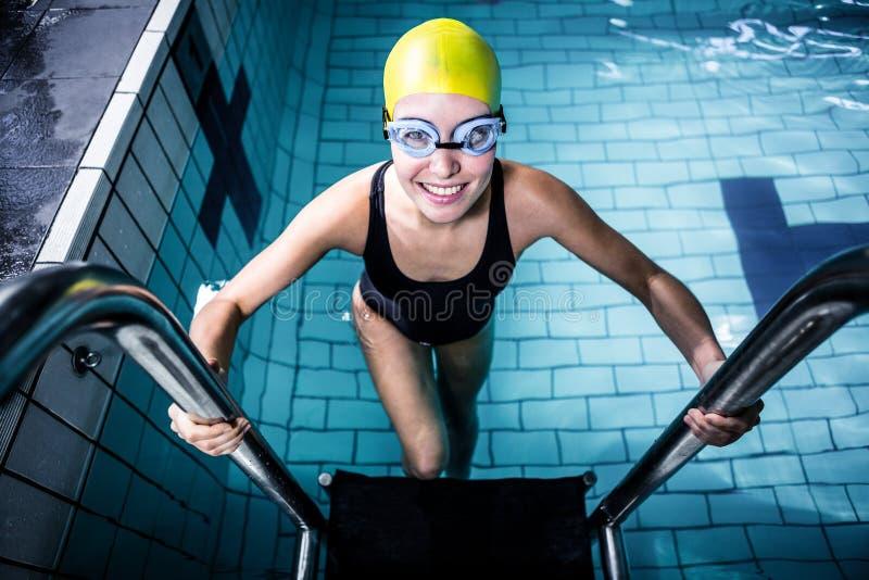 Glimlachende zwemmersvrouw die van het zwembad weggaan stock fotografie